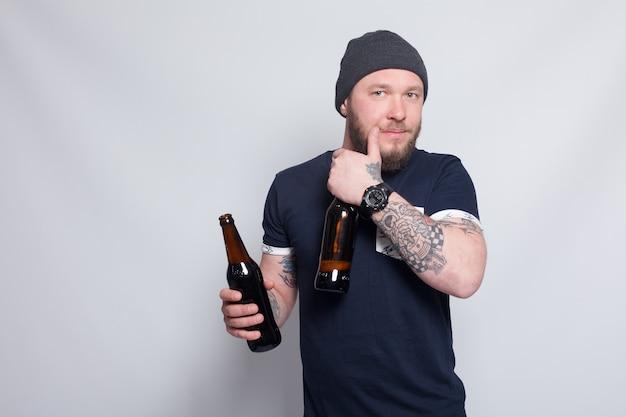 Люди, 4k и концепция образа жизни - брутальный бородатый мужчина с татуированной рукой пьет пиво из бутылки. красивый мужчина в шляпе. жестокий бородатый мальчик с татуировкой
