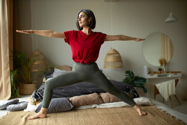Concetto di persone, attività, salute e vitalità. elegante giovane donna a piedi nudi che si esercita a casa, facendo yoga flusso vinyasa nella sua camera da letto, in piedi sul tappeto in virabhadrasana o guerriero ii pongono