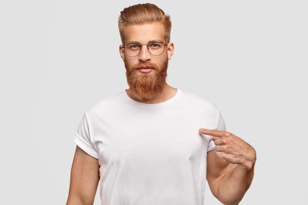 Concetto di persone, pubblicità e abbigliamento. hipster uomo serio con taglio di capelli alla moda e barba rossa, indica uno spazio vuoto della sua maglietta