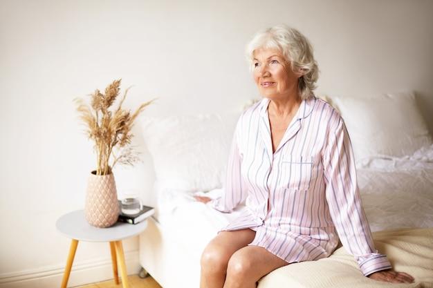 사람, 나이, 침구 및 취침 개념. 평화로운 편안한 수석 은퇴 한 여성의 실내 촬영은 실크 잠옷에 침대에 앉아 새로운 하루의 시작을 기대합니다. 잠이 성숙한여 인