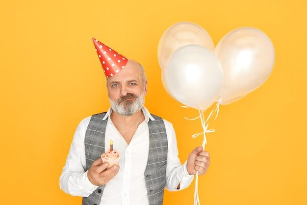 사람, 나이, 축하 및 휴가 개념. 심술 노인 사업가의 수평 샷 풍선, 원뿔 모자와 컵 케이크와 격리 된 포즈, 그의 은퇴를 축하, 불쾌한 표정을 갖는