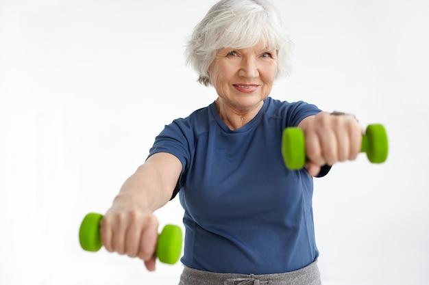 人、年齢、エネルギー、強さ、幸福の概念。緑のダンベルを使用して、朝に体操をしているtシャツを着ている愛らしい笑顔の女性年金受給者。セレクティブフォーカス