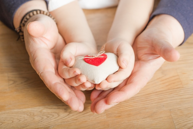 People, age, family, love and health care concept - close up of senior woman and little boy hands holding red heart over wooden background