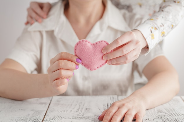 People, age, family, love and health care concept - close up of senior woman and young woman hands holding red heart