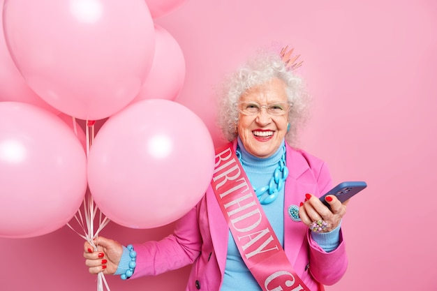 People age festive holiday concept. positive good looking european female pensioner chuckles positively holds modern smartphone gets messages of congratultaion holds bunch of inflated balloons
