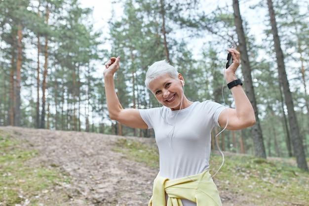 사람, 나이, 재미 있고 활동적인 라이프 스타일 개념. 스마트 폰을 사용하여 실행중인 재생 목록을 듣고 행복 중간 나이 든된 여자.