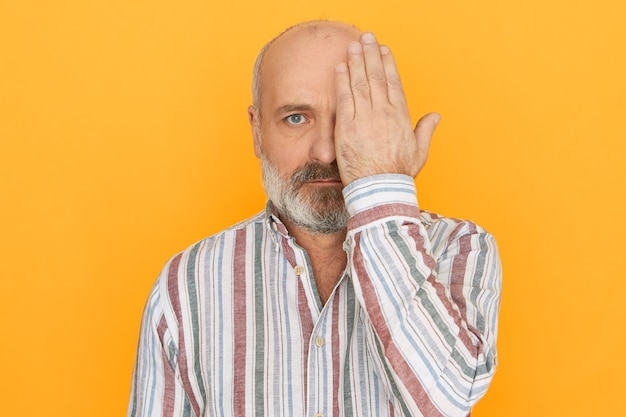 People, age, health and retirement concept. unshaven bald retired man in striped shirt covering one eye with hand having vision tested in ophthalmology clinic, not able to see nearby objects