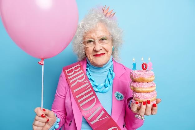 Concetto di evento festivo di vacanze di età della gente. la bella donna anziana con la faccia rugosa dei capelli ricci tiene le ciambelle smaltate il palloncino gonfiato festeggia il compleanno