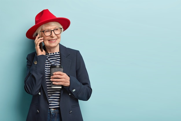 People, age and leisure concept. happy old lady enjoys spare time, has telephone conversation, drinks coffee to go, wears red headgear and formal coat, looks aside, models over blue wall, free space
