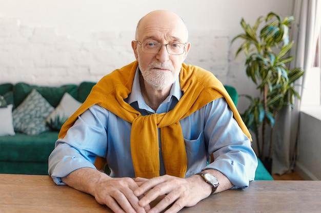사람, 나이, 라이프 스타일 및 패션 개념. 직사각형 안경, 손목 시계, 파란색 셔츠와 노란색 스웨터를 입고 잘 생긴 형태가 이루어지지 않은 대머리 수석 남자가 나무 책상에 앉아 카메라를보고