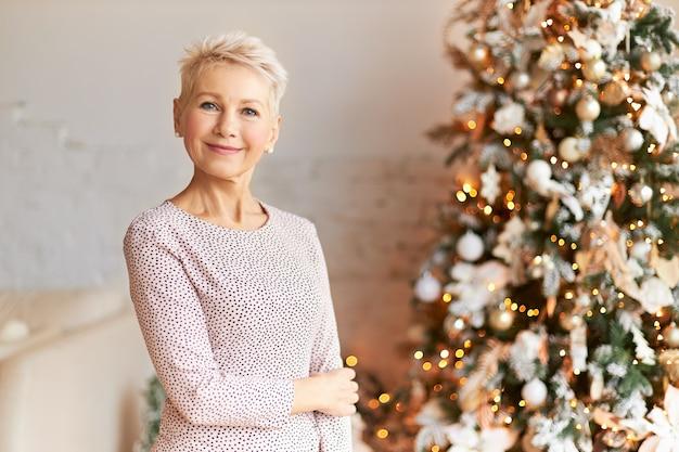人、年齢、ライフスタイル、喜び、幸福、お祭り気分のコンセプト。新年を祝うホリデードレスを着て、幸せな表情をして、クリスマスツリーでポーズをとってファッショナブルな60歳のブロンドの女性