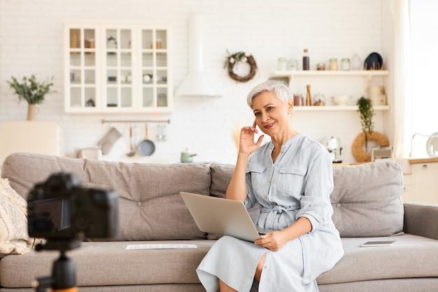 사람, 나이, 성숙도 및 현대 기술 개념. 거실의 소가에 비디오를 녹화하는 세련된 짧은 머리 여성 블로거의 실내 촬영, 노트북 키보드 입력, 삼각대에 고정 된 모습