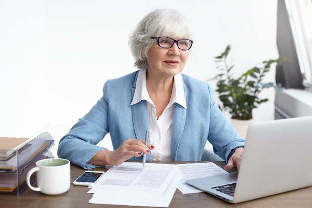 人、年齢、成熟度、仕事、職業の概念。思慮深い表情で、一般的なポータブルコンピューターで紙とキーボードを勉強している美しい自信を持って年配の女性弁護士の屋内ショット