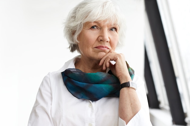 People, age, maturity and lifestyle concept. portrait of stylish serious mature businesswoman with short white hair touching chin, having pensive look, thinking about business plans and ideas
