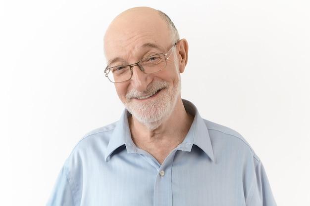 Люди, возраст, позитив, концепция радости и счастья. красивый милый пожилой мужчина в синей рубашке и прямоугольных очках широко улыбается, смеется над собственной шуткой, выражая положительные эмоции