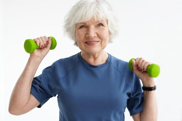 人、年齢、スポーツ、アクティブなライフスタイルのコンセプト。ジムでフリーウェイトで運動をしているtシャツの幸せなポジティブ成熟した引退した女性の写真。ダンベルで興奮したシニア女性のトレーニング