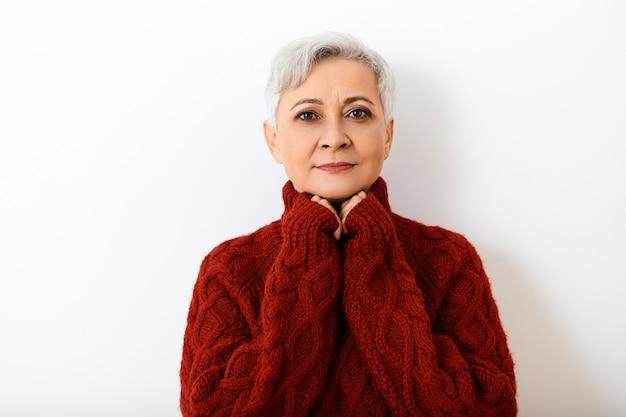人、年齢、スタイル、ファッション、季節のコンセプト。彼女のあごの下で手をつないで、ニットのセーターを着て笑っている短いピクシー髪型の美しい幸せなシニア60歳の女性の写真