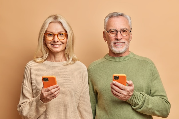 People age and technology concept. portrait of middle aged woman and man hold smartphones,