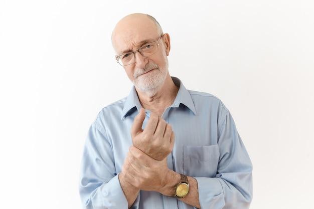 사람, 나이, 웰빙, 질병 및 건강 문제 개념. 고통스러운 표정, 손목을 문지르고 관절 통증으로 고통받는 안경에 좌절 된 60 세의 남자의 스튜디오 샷