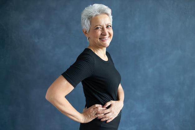 人、老化、成熟度、ライフスタイルのコンセプト。身体活動をしている、彼女の腰に手を離してポーズをとって、笑っている黒いタイトなトップの陽気な大喜びの成熟した女性のスタジオ画像