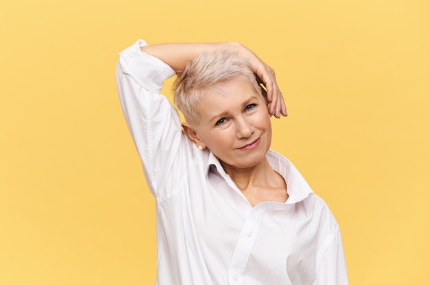 사람, 노화, 성숙, 미용, 피부 관리 및 건강 개념. 픽시 염색 이발 머리를 굽히고 운동을하는 뺨에 손을 잡고 아름다운 세련된 성숙한 여성, 미소