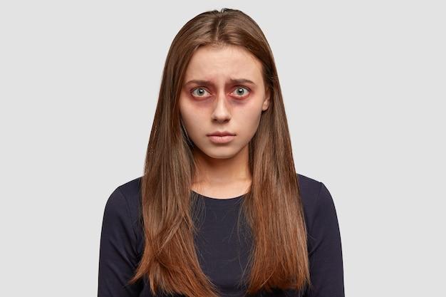 Люди и концепция избили. ушибленная темноволосая молодая женщина, ставшая жертвой жестокого мужчины, отчаянно смотрит в камеру
