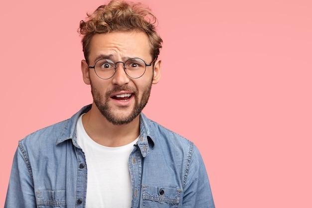 人と戸惑いのコンセプト。困惑した無精ひげを生やした白人男性が意外と眉を上げ、何かに感動し、白いtシャツとデニムシャツを着て、ピンクの壁にポーズをとる