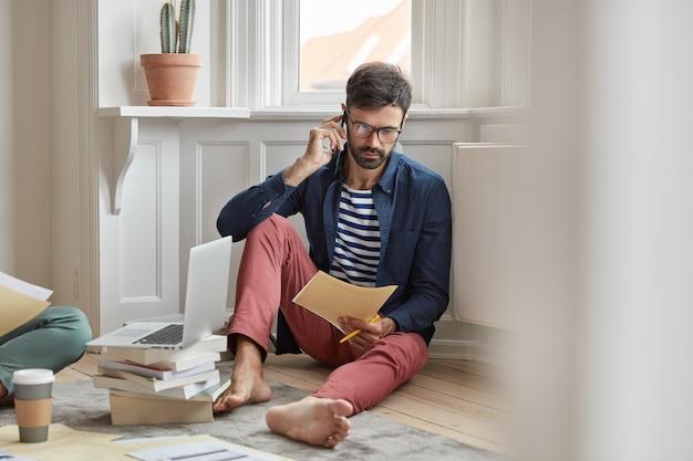 人とビジネスの概念。無精ひげを生やした男性従業員は、より良い解決策を考え、スマートフォンを介して話し、ドキュメントを読みます
