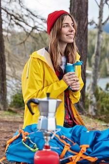 사람과 캠핑 개념. 만족 한 여성 여행자는 하이킹 후 보온병에서 뜨거운 음료를 마신다