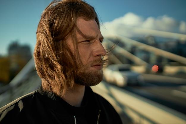 人と都市のライフスタイルのコンセプト。乱雑な赤い髪と都市の風景の背景に鼻ピアスのposignを持つ魅力的なスタイリッシュなひげを生やした男の肖像画、真剣に自信を持って見える