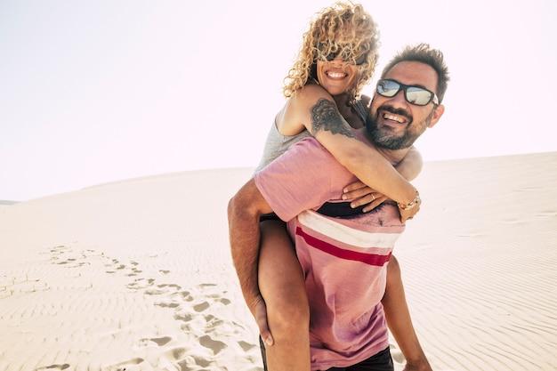 愛する人やカップルは、休暇中にビーチで砂漠の砂丘を楽しんで楽しんでいます。男は笑顔と笑いの美しい巻き毛の女性を背負っています。旅行先と幸せ