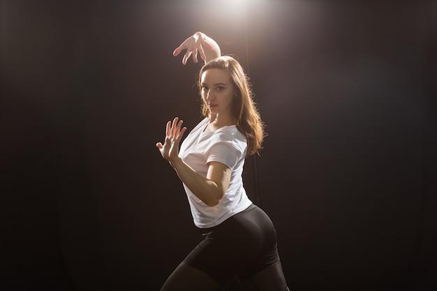 사람과 춤 개념 - 스튜디오에서 거리 춤을 추는 젊은 운동 여성의 클로즈업.