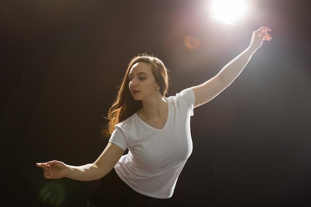 사람과 춤 개념 - 검은 스튜디오 배경에서 재즈 펑크를 춤추는 젊은 아름다운 스포티 여성.