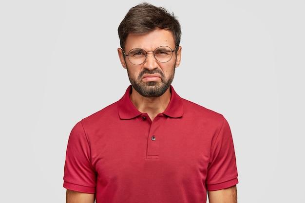 Люди и неприязнь к себе. недовольный молодой бородатый мужчина хмурится, у него темная щетина, недовольное выражение лица, видит что-то неприятное, носит повседневную красную футболку, изолирован на белой стене