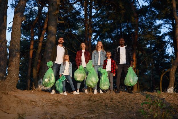 Концепция людей и экологии - группа счастливых добровольцев с зоной очистки мешков для мусора в парке