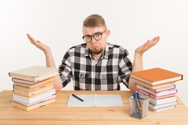 Люди и концепция образования - запутанный студент человек, сидящий за деревянным столом с книгами и