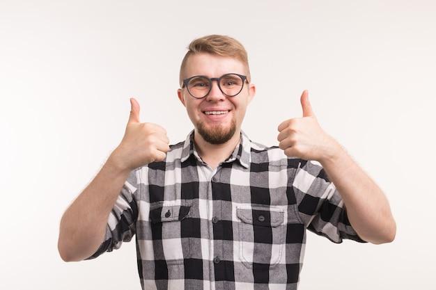 Люди и концепция образования - улыбающийся студент, жестикулирующий большими пальцами над белой стеной