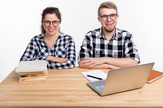 人と教育の概念。テーブルに座っている格子縞のシャツを着た2人の学生