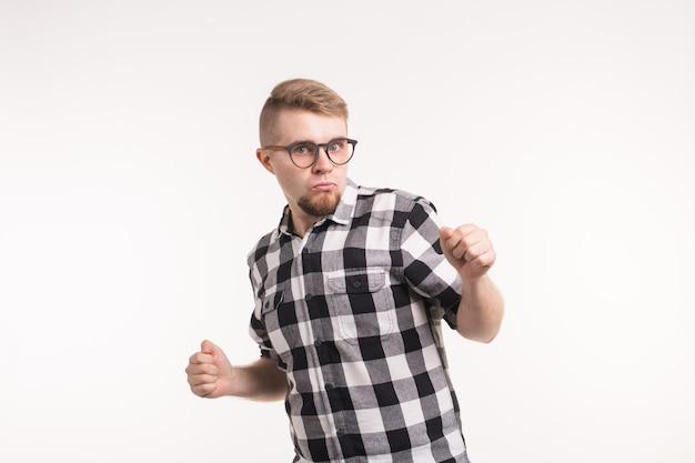 Концепция людей и эмоций - красивый молодой человек в клетчатой рубашке смешно танцует на белом фоне