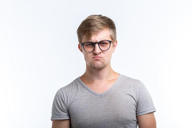 Концепция людей и эмоций - несчастный забавный человек, изолированные на белой стене