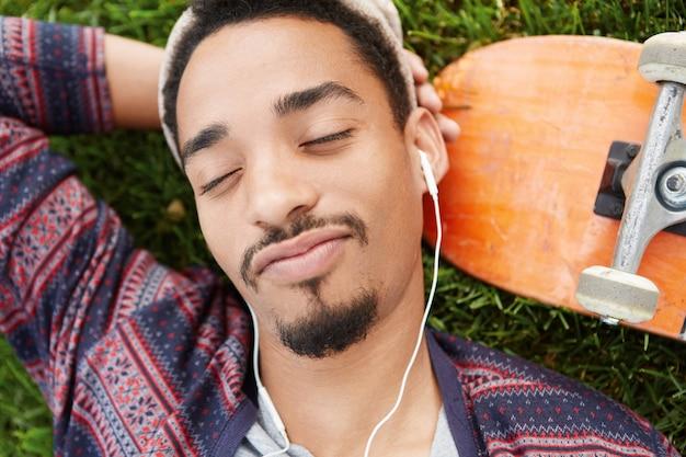 人と楽しみのコンセプトです。ひげを生やしたスタイリッシュな男性のクローズアップは喜びで目を閉じ、白いイヤホンでお気に入りの曲を聴いて、