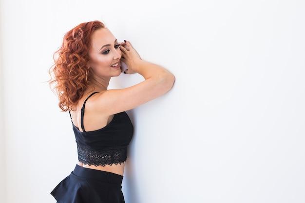 人とファッションのコンセプト-白い壁に隔離された黒いシャツとスカートのポーズで赤毛の女性。