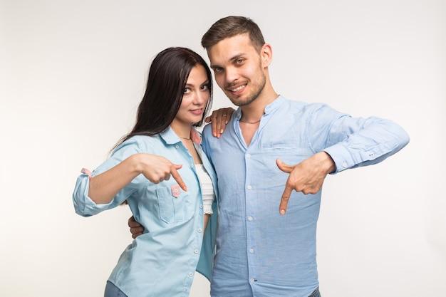 人とジェスチャーの概念-白い背景の上に下向きの若いきれいな女性とハンサムな男。
