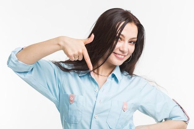 人とジェスチャーの概念-白い背景の上に下向きの若いきれいな女性。