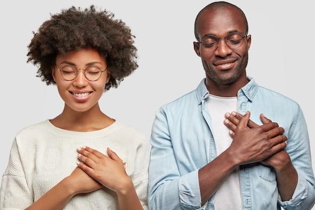 사람과 감사 개념. 꽤 젊은 아프리카 계 미국인 여성과 어두운 피부를 가진 남성의 가로 샷은 가슴에 손을 대고 그들을 도운 사람들에게 감사하고 매력적인 미소를지었습니다.