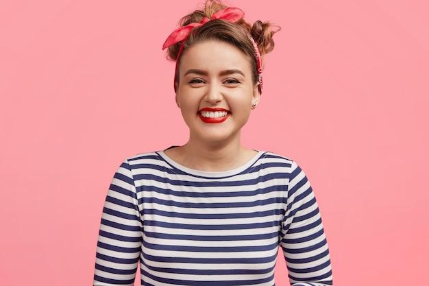人と幸福の概念。セーラーセーターを着た愛らしい若い笑顔の女性は、楽しい話に満足して、ピンクの壁に立っています。うれしそうなピンナップガールがポジティブさを表現