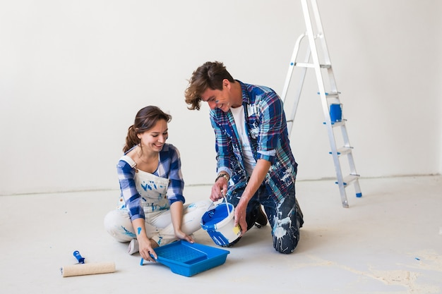 人とインテリアのコンセプト-白い床に座ってペンキを注ぐ若いカップル