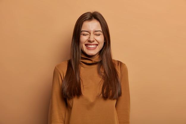 사람과 기쁨 개념. 기뻐하는 검은 머리 성인 여성은 눈을 감고 행복하게 웃고, 친구와 자연스럽게 이야기하고, 웃음을 참을 수 없으며, 캐주얼 터트 넥을 입으며, 갈색 벽에 격리됩니다.