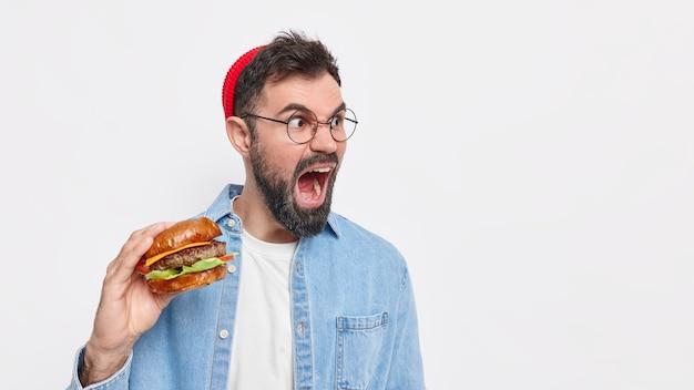 사람과 정크 푸드 개념. 감정적 인 수염을 기른 유럽인 남자가 크게 비명을 지르며 입을 크게 벌리고 미친 표정을지었습니다 맛있는 햄버거를 입고 모자 denimm 셔츠와 둥근 안경
