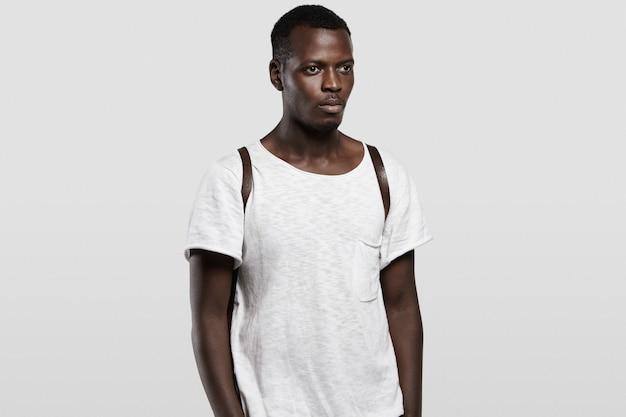 人とライフスタイル。革のリュックサックと広告用のコピースペース付きの白いtシャツを着ている魅力的な若いアフリカの流行に敏感な学生。